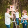 Happy family with Wooden birdhouse — Stock Photo #63884805