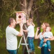 Happy family with Wooden birdhouse — Stock Photo #63885111