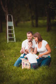 Happy family with nesting box and paints — Stock Photo