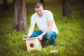Man with wooden birdhouse — Stock Photo