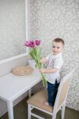 Cute baby boy with tulip — Stock Photo