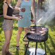 Two pretty girls making food on grill — Stock Photo #53124441