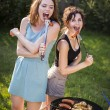 Two pretty girls making food on grill — Stock Photo #53124453