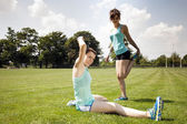 Two young girls stetching before a jogging — Stock Photo