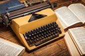 Old typewriter, a pile of books and a lot of creativity — Stock Photo