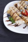 Delicious sweet rolled pancakes on a plate with fresh fruits — Stock Photo