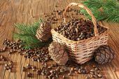 Cedar nuts in a wicker basket on a wooden table — Stock Photo