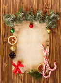 Christmas decorations on the old sheet of paper on a wooden back — Photo