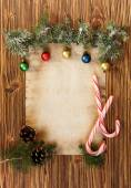Christmas decorations on the old sheet of paper on a wooden back — Stock Photo