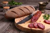 Salami, bread and a knife on the  table — 图库照片