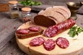 Salami en rodajas y el pan sobre una tabla de cortar — Foto de Stock