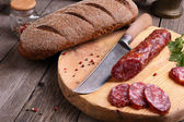 Salami, bread and a knife on the  table — Stock Photo