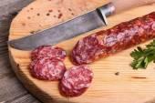 Salami and knife on a cutting board — 图库照片