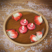 Spa concept with rose petals, salt and burning candles that floa — Stock Photo