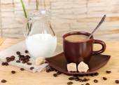A cup of coffee with cream and jug cream on a wooden table — Foto Stock