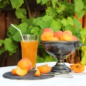 Apricots in a metal vase and a glass of apricot juice — Stock Photo