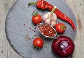 Ketschup Chili in einer Sauciere Glas und seine Zutaten auf ein bla — Stockfoto