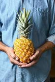 Man Holding Ripe Pineapple — Stock Photo