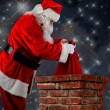 Santa Putting Bag into Chimneys — Stock Photo #58157231