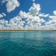 White fluffy clouds blue sky above a surface of the sea — Stock Photo #70666079