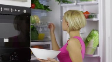 Woman gets vegetables from fridge — Stockvideo