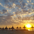 Sunset over the beach with reed umbrellas — Stock Photo #62679073