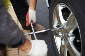 Car mechanic changing tire. — Stock Photo