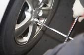 Car mechanic changing tire. — Stock Photo
