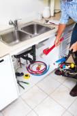 Plumber on the kitchen. — Foto de Stock
