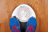 A pair of man's feet standing on a scale — Stock Photo