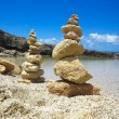 Piramide stack of zen stones near sea and blue sky — Stock Photo #80279032