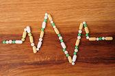 Heap of pills on wooden desk — Stock Photo