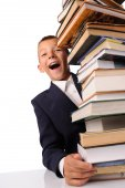 Surprised schoolboy with huge stack of books — Stockfoto