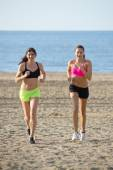 Two women running on beach — Стоковое фото