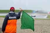 Marshal waving a green flag — Photo