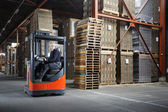 Man driving reach truck in a warehouse — Stock Photo