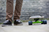 Skateboarder feet and skateboard in urban setting — Stock Photo