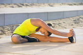 Flexible woman stretching on a beach boulevard — Stock Photo