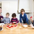 Mother and children decorating cupcakes — Stock Photo #62424883