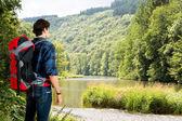 Hiker walking along a river — Stock Photo