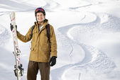 Young off piste skier standing in front of fresh tracks — Stock Photo