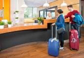 Young travelers at hotel check in — Stock Photo