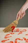 Hand sweeping question marks from the floor — Stock Photo