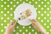Woman eating fifty euroes banknotel for dinner — Stock Photo