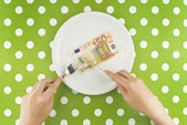 Woman eating fifty euroes banknotel for dinner — Stok fotoğraf