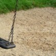 Empty swing seat swaying at playground in the park. — Stock Video #53397075