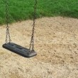 Empty swing seat swaying at playground in the park. — Stock Video #53398589