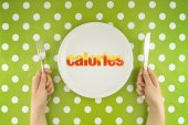 Hands at the table with calories on plate — Stock Photo