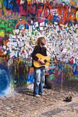 Street Busker performing in front of John Lennon Graffiti Wall — Stock Photo