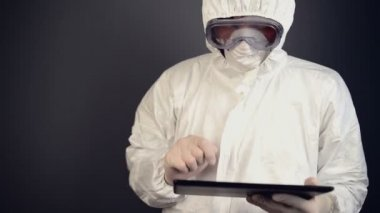 Chemical scientist in protective clothing using digital tablet for computing. — Stock Video